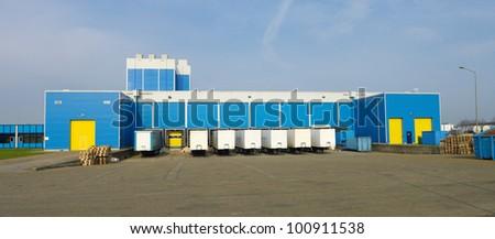 modern blue warehouse with loading docks - stock photo