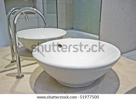 modern bowl shape ceramic hand wash basin with designer water tap - stock photo