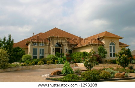 modern brick and stucco house with extensive landscaping and plantings in front - stock photo
