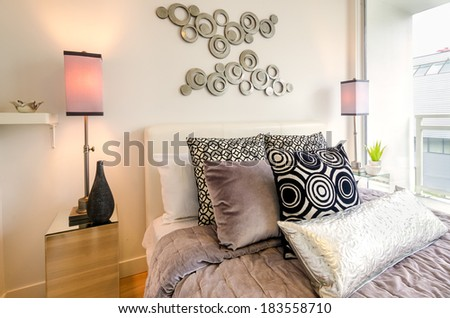 Modern bright bedroom interior with designer pillows in a luxury house