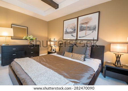 Modern bright bedroom interior with designer pillows in a luxury house, hotel.