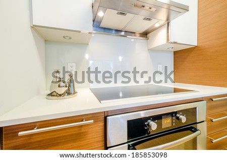 Modern, bright, clean, kitchen interior with stainless steel appliances and wooden cabinets in a luxury house - stock photo