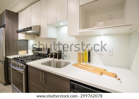 Modern, bright, clean kitchen interior with stainless steel appliances in a luxury apartment. - stock photo