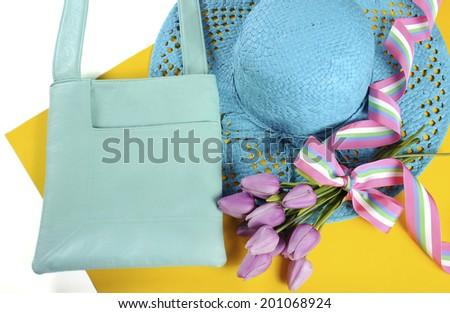 Modern bright Sixties mod style color blocking design for ladies fashion accessories in aqua blue with sun hat, and shoulder strap handbag with flowers.