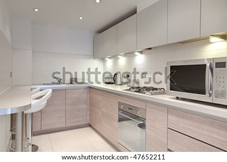 Modern brightly lit kitchen with fitted appliances - stock photo