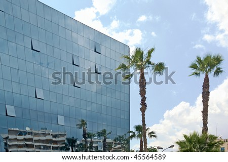 Modern building at glass wall and two palm tree against a deepening blue sky with cloud in Limassol, Cyprus - stock photo