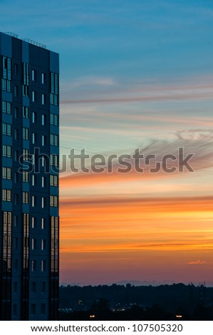 Modern building at sunset with beautiful cloudscape at background - stock photo