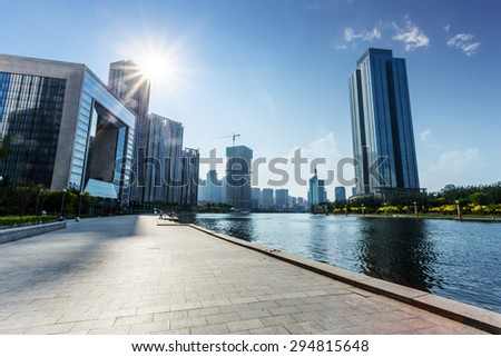 modern building exterior with brick road floor at riverbank - stock photo