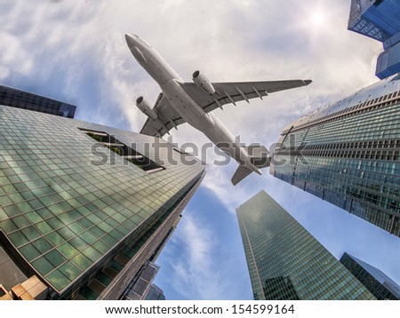 modern building with airplane under the sky - stock photo