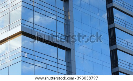 Modern building with glass windows reflected sky