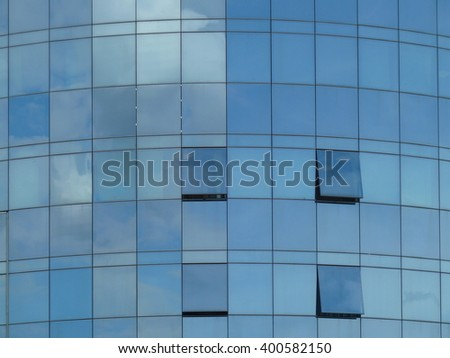 Modern building with reflections from the sky and  opened windows