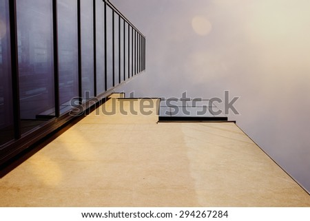 Modern building with wall and glass elevator shaft, sun shine and flare.  - stock photo