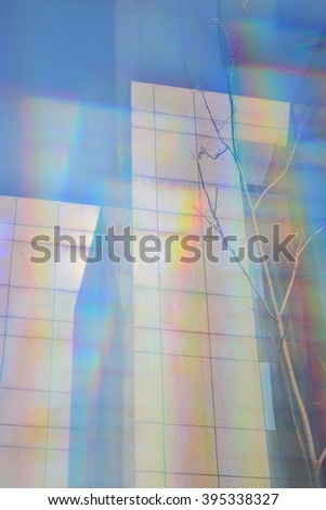 Modern buildings facade and tree branches abstract colorful blur through prism filter.