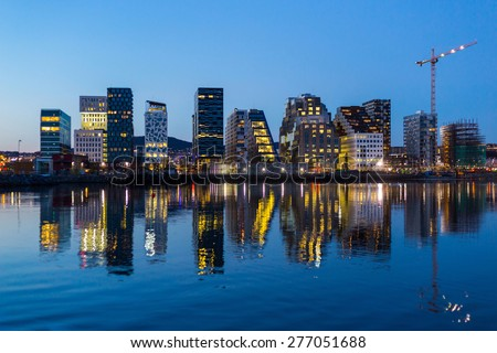 Modern buildings in Oslo at twilight with their reflection into the water. These are some of the new buildings in the neighbourhood of Bjorvika. - stock photo