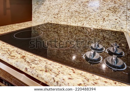 Modern built-in stove with shiny black flat surface. Granite counter top. - stock photo