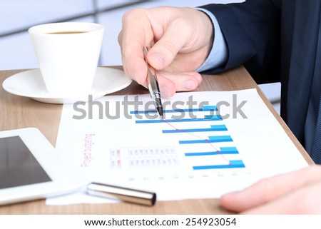 Modern business man  doing business, graphs and charts behind - stock photo