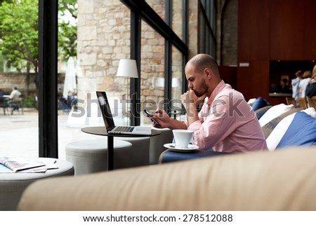 Modern business man using smart phone and laptop computer in light loft interior,young hipster busy using smart phone in hotel hall,male student reading message on phone sitting at sofa of coffee shop - stock photo