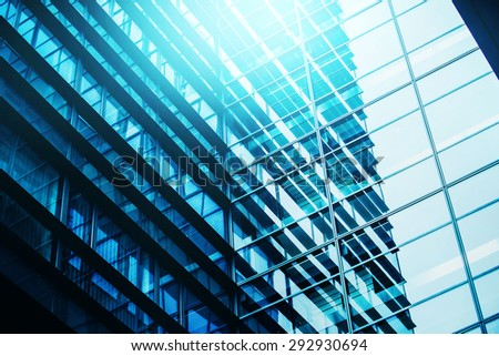 Modern Business Office Building Windows Repeating Pattern, Blue Glass Facade with Geometric Lines, Sunlight Reflecting - stock photo