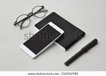 Modern business on the go- smart phone, notebook,  eyeglasses, and pen, isolated