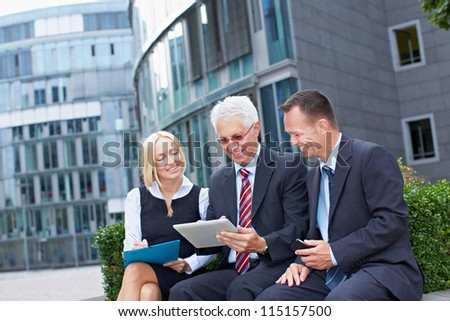 Modern business team working outside the office with tablet PC - stock photo