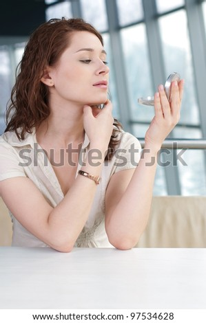Modern business woman doing make-up at lunch time - stock photo