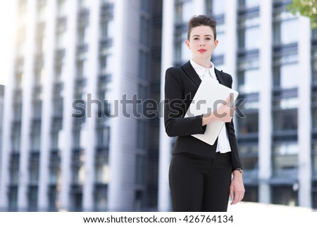 Modern business woman holding laptop