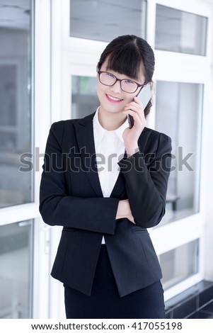 Modern business woman in the office, talking on phone