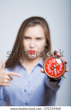 Modern business woman pointing to the alarm clock, isolated - stock photo