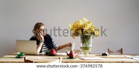 Modern business woman reading a newspaper while having discussion on the smart-phone. attractive young blonde woman put down the laptop and enjoy the morning paper and tea - stock photo