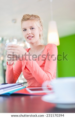 Modern business woman sitting at his desk and reading a text message on her smartphone, cup of coffee at foreground - stock photo