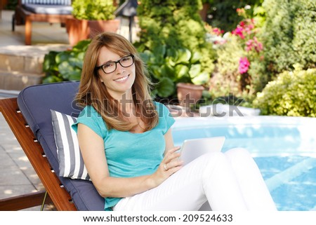 Modern business woman with digital tablet sitting at garden and working at home. Small business.