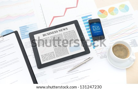 Modern business workflow with digital computer, mobile phone and some papers with charts and numbers on a desktop. - stock photo