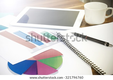 Modern business workplace on digital tablet, mobile banking on a smartphone and some charts and graphs on a desktop. - stock photo