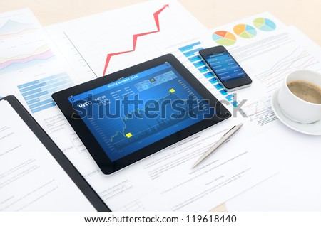 Modern business workplace with stock market data application on a digital tablet, mobile banking interface on a smartphone and some papers with charts, graphs and numbers on a desktop. - stock photo