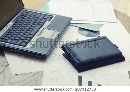 Modern business workplace with tablet, laptop and some papers with charts, graphs and numbers on a desktop.  - stock photo