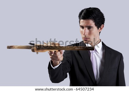 Modern businessman aiming with a crossbow (isolated on gray) - stock photo