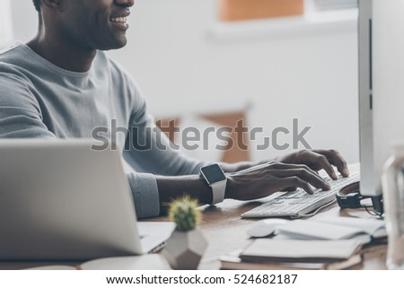 Modern businessman at work. Close-up of handsome young African man working on the computer and smiling while sitting at his working place in home office