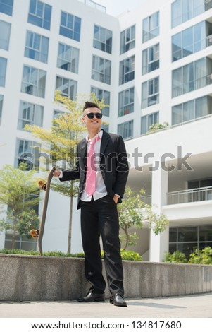 Modern businessman enjoying his after-work hobby of skating and listening to music