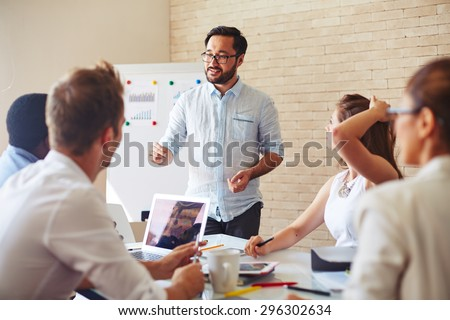 Modern businessman explaining his ideas to colleagues at seminar