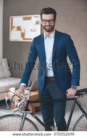 Modern businessman. Handsome young man wearing glasses and suit looking at camera with smile while standing with retro bicycle in office  - stock photo