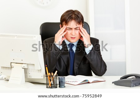 Modern businessman with headache sitting at office desk and holding hands at head