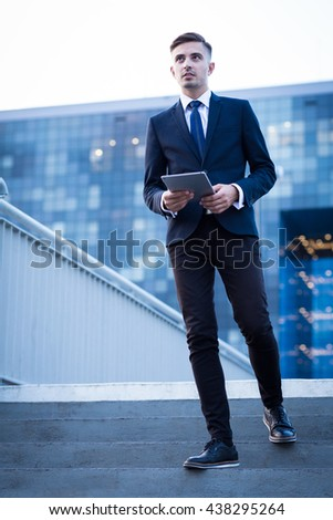 Modern businessman with tablet, modern building in the background