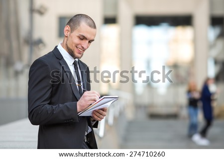 Modern businessman. Young man of arabic origin in a suit. Business man in the background office building. Confident businessman portrait. Confident and charismatic modern business man. Note pad record - stock photo