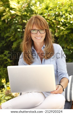 Modern businesswoman sitting at garden and working at home with laptop. Business people.