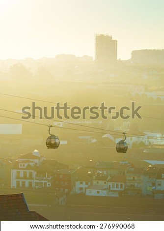 Modern cable cars in Porto at sunset. Gaia city on the background. Portugal - stock photo