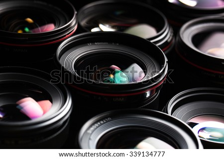 Modern camera lenses with reflections, low key image