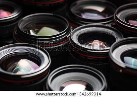 Modern camera lenses with reflections, low key image - stock photo