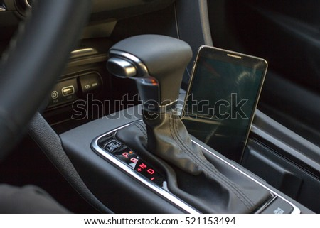 Modern car interior with smart phone on gear stick.