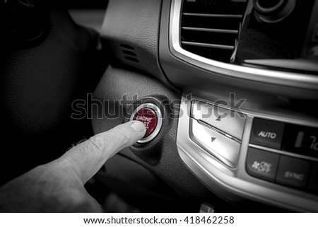 Modern car start and stop button, with a finger tip in front of the engine start stop button inside a car. The start stop engine is in red, beside the start stop engine color shade in black and white