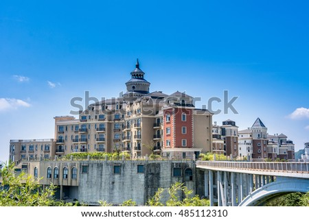 Modern castle on the top of mountain with bridge against blue sky.